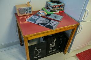 Här i köket ett bord med plastlaminerad perstorpsskiva, ny radio och återvinning under, och  50-talsstuk på duken.