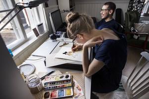 Robert och Anna sitter tillsammans och skapar vid deras skrivbord i Ljusdal.