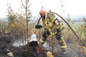 Brandmannen Brian Ringsted-Pedersen ser till så att marken är ordentligt släckt.