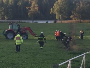 Räddningstjänsten jobbar på plats med att lyfta hästen med hjälp av selar och traktor.
