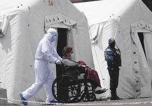 En kvinna sjuk i covid-19 förs till ett sjukhustält i Quito i Ecuador.