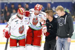 Patrick Dwyer och Magnus Håkansson hjälper Peter Öberg av isen i Kinnarps Arena.