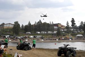 En Black Hawk flyger över tävlingsområdet.