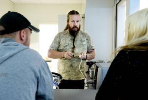 Tommy Nordlund jobbar med inredningen av cafédelen och mikrovågsugnens placering. Här i samråd med Ulf Jansson och Ann Öberg.