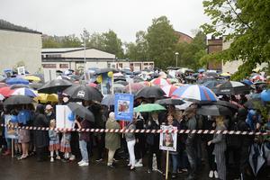 Föräldrar, syskon och vänner väntade snällt under sina paraplyer.