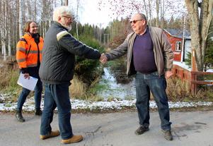 Staffan Korsgren (L) ordförande i Kultur- och tekniknämnden i Askersund och Conny Larsson (S), ordförande i Drift- och servicenämnden i Hallsberg, skakar hand på gränsen mellan de två kommunerna. Gränsen går vid Toskabäcken. De två kommunerna samarbetar nu när det gäller dricksvattenförsörjning för områdena längs med Tisarens norra strand. Med på bilden är även Tove Dahlström, projektledare för utbyggnaden av vatten- och avloppsnätet vid Tisarens norra strand.