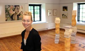 Lisa Ling är curator för utställningen, som visas både inne i Stenkvarnen och ute i slottsparken. I bakgrunden en av hennes målningar.