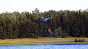 Helikoptrar hämtar vatten för att kunna släcka branden.