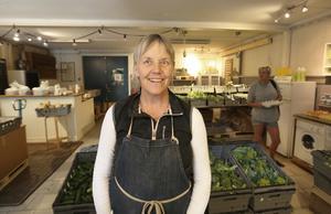Meta Wålstedt i Gårdsbutiken bland grönsaker och kunder.