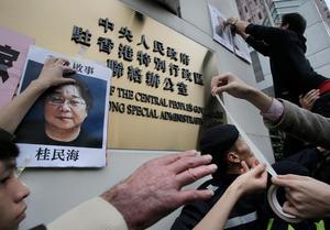 Bilder av den frihetsberövade bokförläggaren Gui Minhai sätts upp i en protest i Hong Kong 2016.