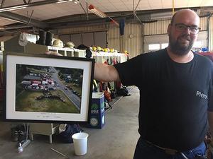 Pierre Hedlund håller upp bilden som tog Nisse Schmidt tog, idag är staben borta och vagnhallen är åter en vagnhall. Däremot ligger det inlagda innertaket kvar, det som byggdes under två arbetsamma nätter.