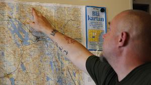 Mikael Bäckman pekar ut platsen på kartan där branden i Skalet är som nu är under kontroll.