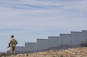 En vakt patrullerar vid den befintliga muren som finns vid en sträckning vid gränsen mellan USA och Mexiko.