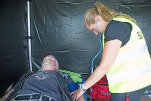 Sjuksköterskan Helena Puggioli kontrollerar blodtrycket på Jonny Hellgren i sjukvårdstältet.