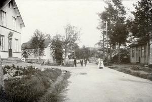 Nynäshamns centrum, tidigt 1900-tal. Centralgatan (Kullstagatan) mot kyrkberget. Huset till vänster har sybehörsaffär, cigarrhandel och telefon. Till höger ett konditori. Bild: Nynäs fotografi atelier/Nynäshamns bildarkiv