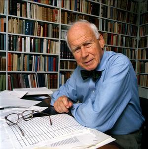 Olof Lagercrantz; journalist och författare.Sitter vid ett bord fullt med papper. På bordet ligger ett par glasögon. I bakgrunden ses bokhyllor med böcker.Foto: Malin Lundberg/SCANPIX