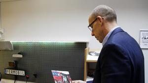 Rikard Rönn studerar ett av  informationsbladen som togs fram för att visa hur bilarna kunde byggas om för att passa de med funktionsnedsättning.