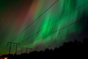 Norrskenet på himlen bakom en kraftledningsgata.