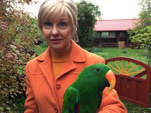 Catrine Tollström tar emot med en av sina favvisar papegojan Lime.