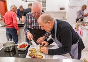 Lars Lund och Tommy Engström kollar så att kycklingköttet är så vitt som det ska vara när det är färdigt.