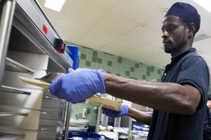 Mamadou Dialloo ställer in en färdig dukad bricka till en patient in i en matvagn.