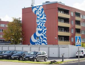 Muralmålningen har placerats ut mot vägen på ett av husen på Vinddraget i Andersberg. Tillsammans med