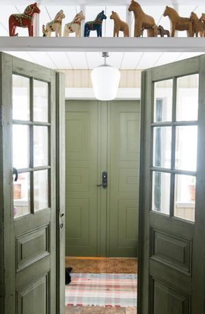 Vackra innerdörrar ut mot farstun. Många gröna nyanser finns i huset.