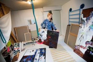 I källaren har hon ateljén där hon målar med duken liggande på golvet.