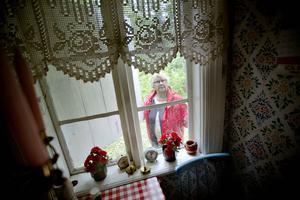 Birgit Karvonen öppnar fönsterluckan till