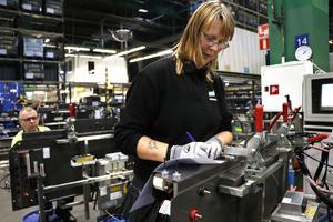 Ann-Sofie Nowén monterar en bakvägg till en förarhytt. Väggen innehåller en stor mängd elektroniska komponenter som måste testas innan väggen monteras på plats. Hon tillhör den del av personalen som är inhyrd via ett bemanningsföretag och har varit på Volvo CE sedan i maj.