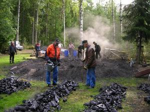Kolet från milan Erika läggs ut i långa rader för att svalna, men det gäller för kolarna att vara på sin vakt, kolet är så hett att det kan ta eld och då gäller det att snabbt vara framme med vattenkannan och släcka elden. Foto:GöstaLjungberg