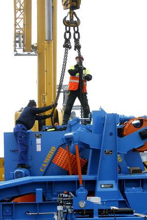 Det krävs precision för att placera barkmaskinen på fundamentet.
