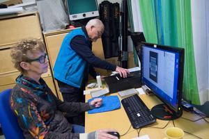 Kristin Ludvigsson sköter datorn medan Edvard Ruin lägger i nya plåtar för scanning.