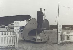 Kommunikationsminister Gösta Skoglund inviger Linjeflygs nya linje: Bromma-Midlanda-Nordmaling inför ett par hundra åskådare. Då var man fortfarande tvungen att åka färja ut till ön, bron kom i slutet av 1959.