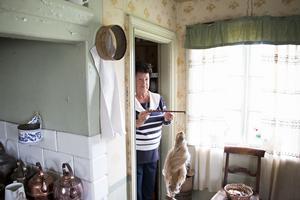 Eva Andersson visar upp en besman som hon hittat inne i det gamla skafferiet i gammelgårdens kök. Den har bland annat använts för att väga hår som såldes till kullor som gjorde hårarbeten.