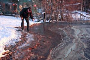 Bengt-Åke Öst känner på den kletiga oljan i en badvik nära Morviken.