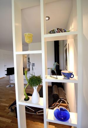 Husets i stort sett enda prydnadssaker är samlade i en hylla i vardagsrummet. Hyllan har också en bärande funktion.