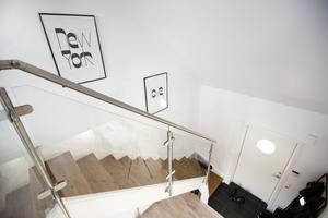 I hallen är det öppet ändå upp till taket. Glasräcket vid trappan förstärker det ljusa intrycket.