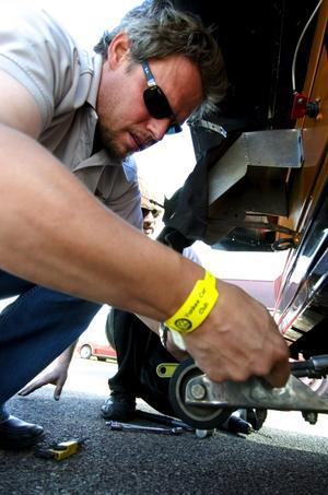 Skydd mot att volta. Mats Göransson hjälper Knasen att montera på stödhjul, för att bilen inte ska slå runt i starten. Foto:Johan Larsson