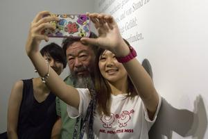 Ai Weiwei poserar för en selfie med en besökare på galleriet i Peking i helgen.