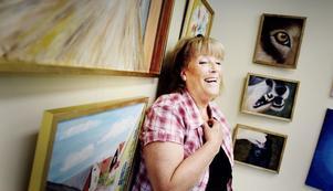 Inga-Lill Arvidsson poserar vid några av hennes egna tavlor.