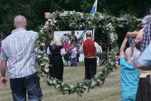 Firandet har börjat och midsommarstången vid Anundshög bärs fram för att resas så att dansen kan komma igång