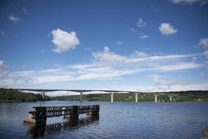 Alnöbron sedd från fastlandet vid det gamla färjelägret 2016. Byggandet av bron började 1961 och den stod färdig 1964. Fram till 1972 var den Sveriges längsta bro med sina 1024 meter i längd. Idag har den halkat ner till plats 14. Viss köbildning blir det dock ibland än idag över sundet.
