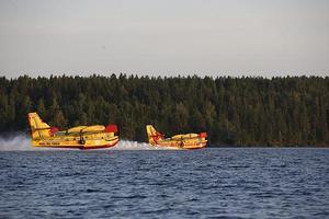 De franska och italienska vattenbombarna tankar vatten på Häredesjön i skogsbrandsområdet. På mindre än tolv sekunder fylls planen med sex ton vatten.