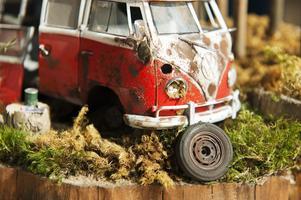 En detaljstudie av Charles Kings modell, rostig folkvagnsbuss i skogen.