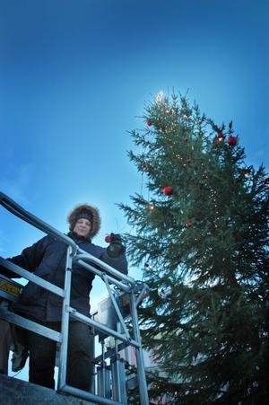 """Tony Warren ägnade hela dagen i går åt att klä granen som står på torget i Ockelbo. Tony har noga mätt ut ett perfekt avstånd mellan alla kulorna och prismorna. """"Så det tar lite tid. Jag hinner inte klart under torsdagen utan får fortsätta hela fredagen också"""", sade Tony i går när mörkret kom och han fick ge upp julpyntandet och ta skyliften ner."""