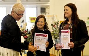 Carin Gisslén-Schönning delar ut stipendium till Linnea Marken, 13, och Sanna Forsling, 14.