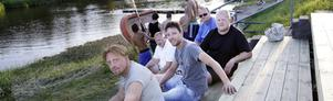 Fina sittplatser. Patrik Porath, Ulf Johansson, Mikael Hedberg, Stickan Carlsson och Thomas Ågren tar en paus i går kväll vid 21-tiden medan ett gäng ungdomar klev ned till badplatsen för ett kvällsdopp.