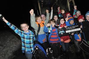 Klass 5 B på Björktjära skola kliver ur bussen och jublar. Här visar de segerchecken. De är bäst i hela länet!