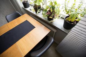 Utfällbart teakbord med stolar i svart plast.